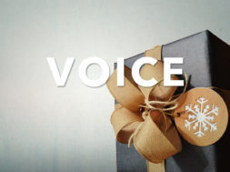 A present in black wrapping paper with a golden bow on top. The word voice in all caps over the image.