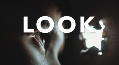 Boy looking through a lit hole in the wall from darkness. The word Look across the image in all caps.