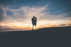 Picture of a couple silhouetted against a beautiful sunset.