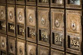 Antique bronze-colored mailboxes with the numbers 574, 584, 604, 614 on them.