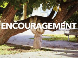 Large tree limb being held up by a huge hand sculpture. It appears the limb may break without the support. The word encouragement is placed over this image.
