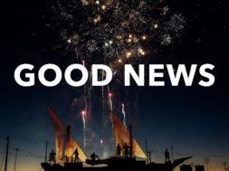 People standing on small sail boats watching fireworks. The words good news over that image.