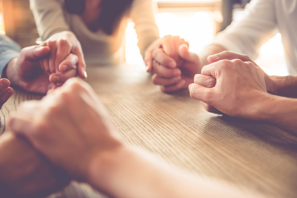 Group of people holding hands and praying at a table.