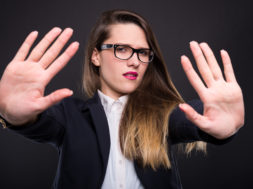 Young beautiful businesswoman with a stop or refusal gesture isolated on dark background