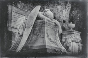 Angel face down on a dais.  Wings and arms draped over the platform.  Black and white image.