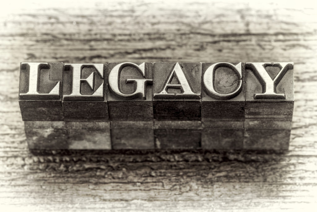 legacy word in mixed vintage metal type printing blocks over grunge wood, black and white image