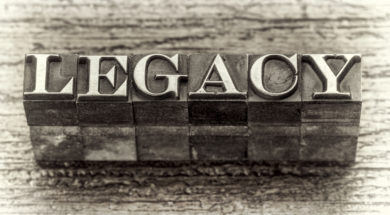 legacy word in mixed vintage metal type printing blocks over grunge wood, black and white image